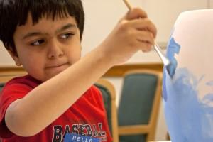 boy painting a vase
